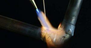 Gros plan sur le brasage d'un tube, à l'aide d'une flamme produite sans gaz
