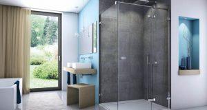 Dans une salle de bains bleue et grise, la douche est équipée d'un paroi Escura de Sanswiss