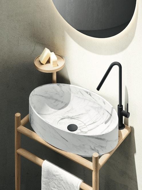 Vasque ovale en marbre posée sur un piétement en bois