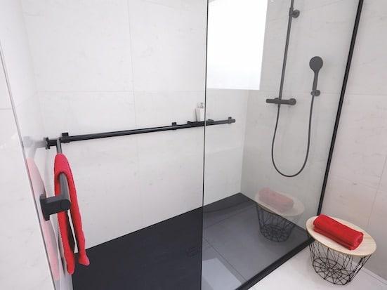 une douche sécurisée avec barres de maintien noires