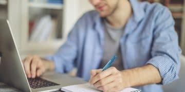 jeune homme travaillant chez lui sur un ordinateur portable