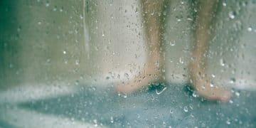 jambes derrière une paroi de douche mouillée