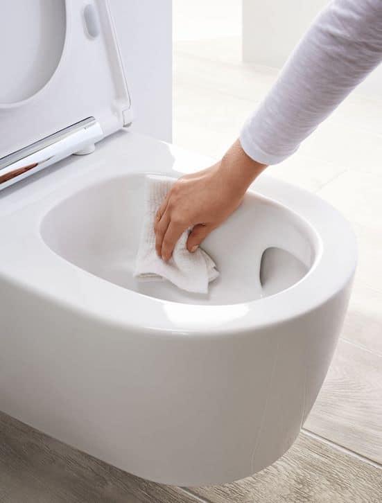 main nettoyant l'intérieur d'un WC suspendu