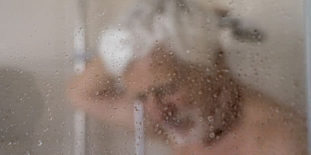 vieux monsieur derrière une paroi de douche embuée