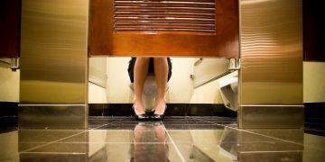 femmes assise sur un WC dans des toilettes publiques