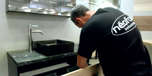 Homme vissant un tiroir de meuble de salle de bains Néoform