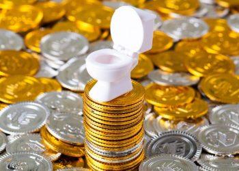 mini WC en plastique posé sur un tas de pièces de monnaie